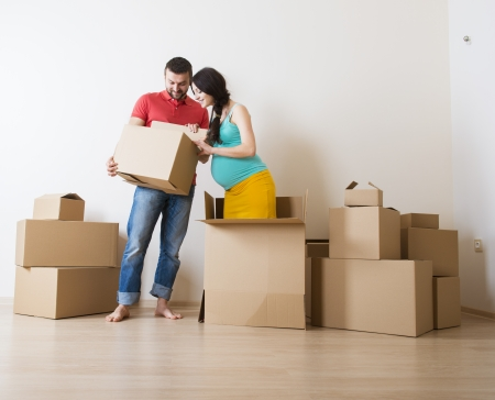 new house: Young couple is moving into new house with lot of boxes  Woman is pregnant