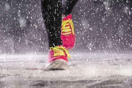 Athlete woman is running during winter training outside in cold snow weather  photo