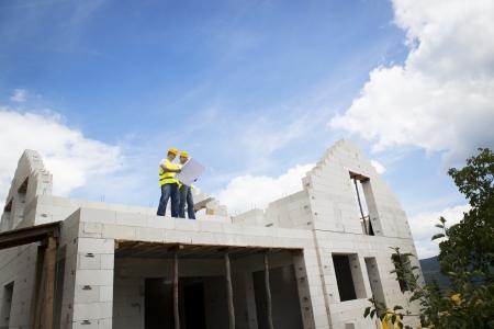 building contractor: Construction Contractors building a big new home Stock Photo