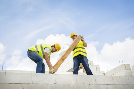 manual worker: Construction Contractors building a big new home Stock Photo