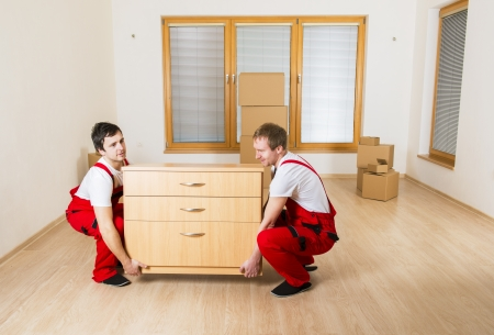 moving box: Movers in new house with lot of boxes behind them