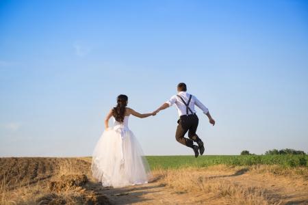 Trouwen paar lopen in een veld onder de blauwe hemel