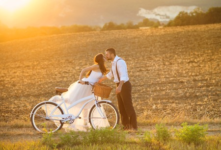 bicycle girl: Beautiful bride and groom wedding portrait with white bike