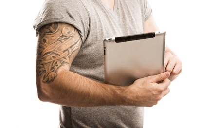 Handsome young man with tattoo is holding digital tablet, isolated on white