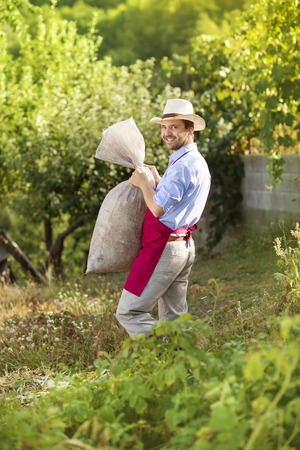 Young male gardener carrying a bag in summer garden photo