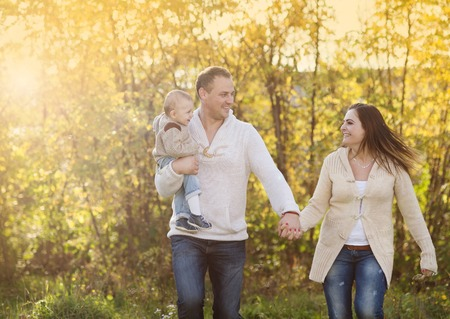 Happy and young family relaxing together in golden and colorful autum nature photo