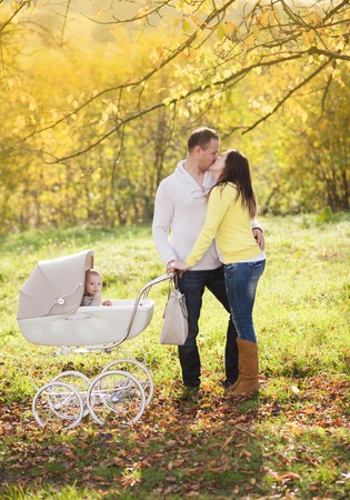 Happy and young family with vintage pram relaxing together in golden and colorful autum nature photo