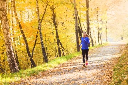 Actieve en sportieve loper vrouw is oefenen in de kleurrijke herfst de natuur