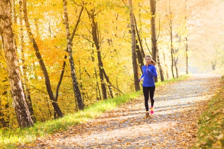 Active and sporty woman runner is exercising in colorful autumn nature