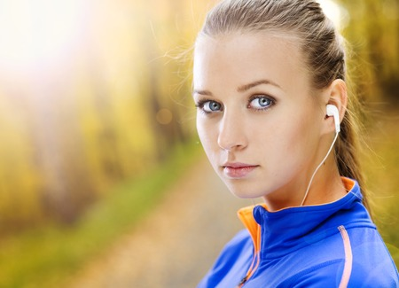 Sporty and active woman runner is listening to music before outdoor exercise photo