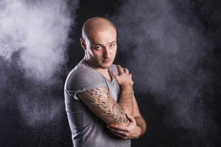 Handsome young man with tattoo, isolated on black  photo