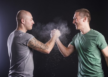 arm tattoo: Two men in studio, isolated on black  Stock Photo
