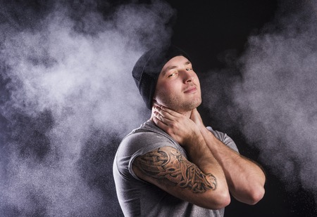 Handsome young man with tattoo, isolated on black  Stock Photo