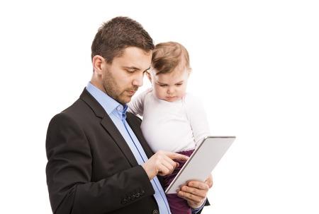 彼の赤ちゃんを持つ男が働いているマネージャーがデジタル タブレットを使用して 写真素材
