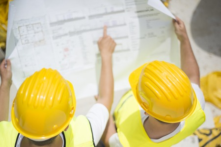 construction management: Engineer builders in safety vest with blueprint at construction site Stock Photo