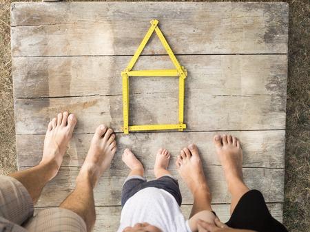 Haus-Konzept mit gelben Meter auf Holzboden