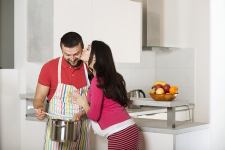 Pregnant woman and happy man in the kitchen photo