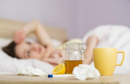 Zieke vrouw ligt in bed met hoge koorts. Ze heeft verkoudheid en griep. Voor haar staat thee met citroen en honing