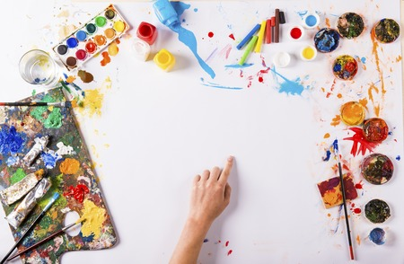 back to work: Creative art concept with colorful paints over white paper