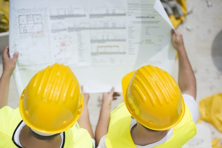 Engineer builders in safety vest with blueprint at construction site photo