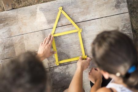 Concetto di casa con la metro gialla sul pavimento di legno