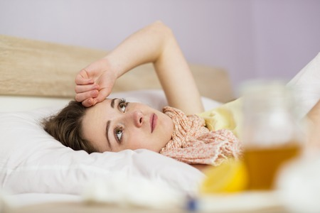 Sick woman lying in bed with high fever  She has cold and flu  In front of her is tea with lemon and honey Stock Photo - 26223862