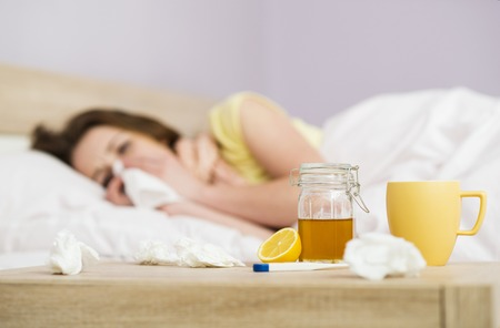 Sick woman lying in bed with high fever  She has cold and flu  In front of her is tea with lemon and honey  photo