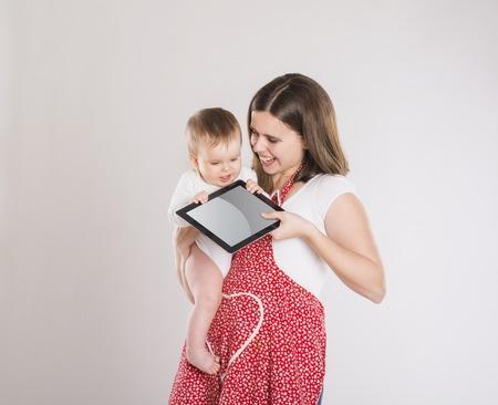madre trabajando: Madre ocupada y el bebé con la tableta digital