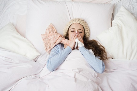 Sick woman lying in bed with high fever  She is blowing nose  Stock Photo - 26337807