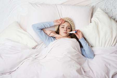 Sick woman with thermometer is lying in bed  She has cold, flu and high fever Stock Photo - 26338287