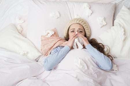 Sick woman lying in bed with high fever  She is blowing nose  photo