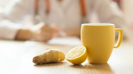 inmunidad: Detalle de la miel, limón y una taza de té con el médico de la mujer en el fondo