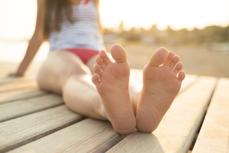 Detail of female barefoot feet on sunny beach photo