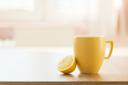 Cup of tea and lemon closeup with sunny house interior in background photo