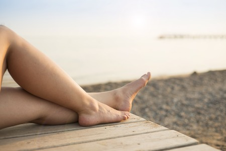 Detail of female barefoot feet on sunny beach photo