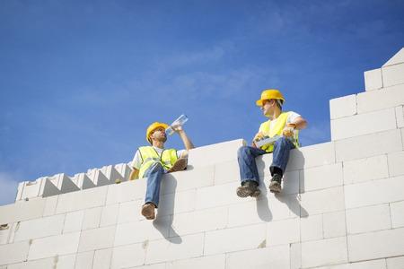 Bouwers werken aan de top van de woningbouw