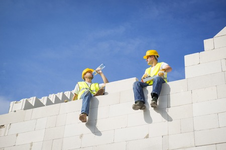 Builders are working on the top of house construction