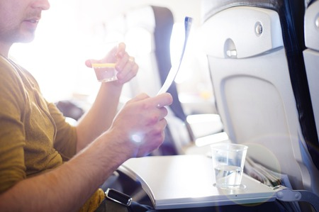 Happy man seating in the aircraft and drinking water before his trip abroad  photo