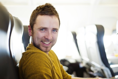 Happy man seating in the aircraft is ready for his flight to holiday abroad photo