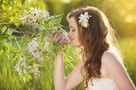 lillac: Beautiful woman with flowers in spring sunshine  Girl is holding a lillac on the green meadow  Stock Photo
