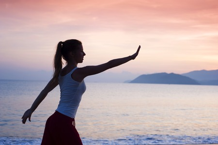 Silhouette of sport active woman stretching and exercising on the beach at sunset  photo