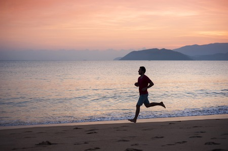 Silhouette of sport active man running and exercising on the beach at sunset  photo