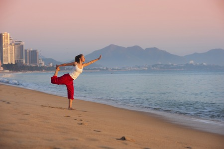 Sport active woman stretching and exercising at the city beach  photo