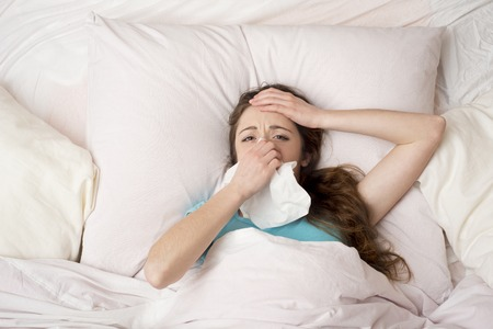 Sick woman lying in bed with high fever  She is blowing nose Stock Photo - 26536713