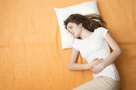 menstruacion: Mujer enferma que est� tumbado en la cama Foto de archivo