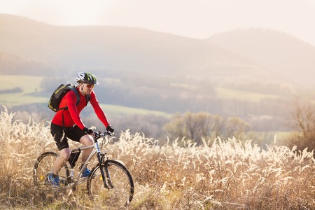 cyclist man riding mountain bike on outdoor trail in nature photo