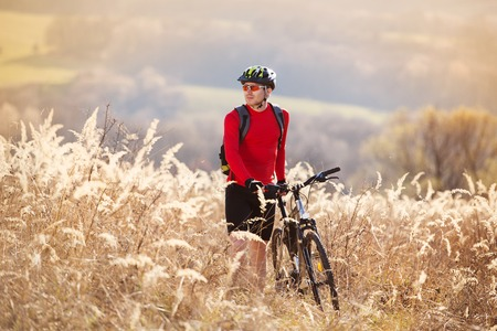 Young man takes a break in a field while mountain biking photo
