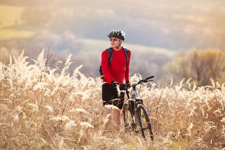 Young man takes a break in a field while mountain biking photo