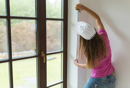 Rear view of young woman measuring the wall with tape measure photo