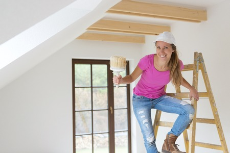 Happy smiling woman painting the walls of new home with paintbrush photo